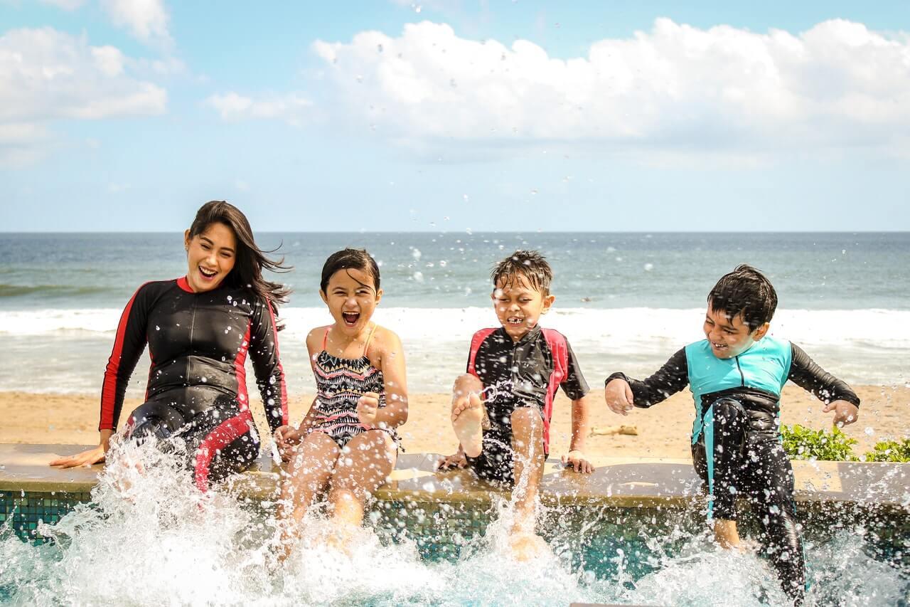 4 crianças brincando com os pés na água da piscina