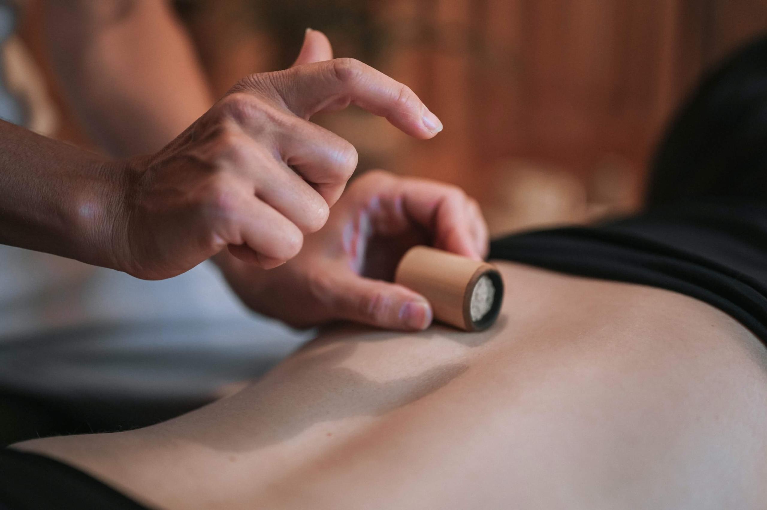 Close em mãos aplicando massagem com pequeno bambu nas costas de uma pessoa