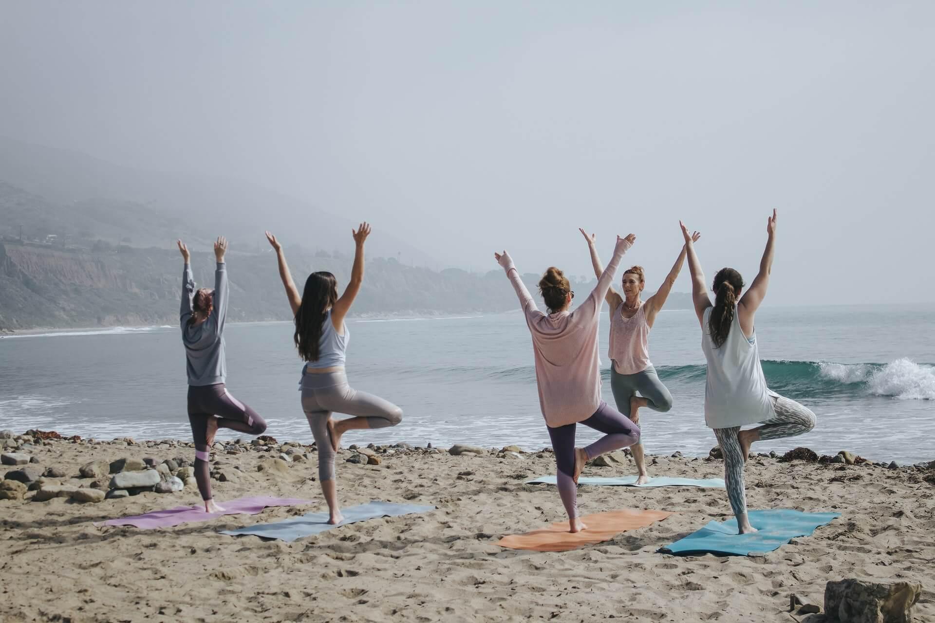 Mulheres praticando yoga na praia